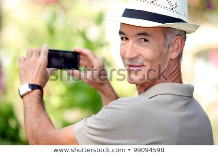 Middle -aged man taking photo whilst wearing straw hat Stock photo © photography33