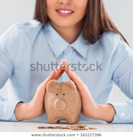 Happy business woman covering piggy bank with two hands - safety stock photo © HASLOO