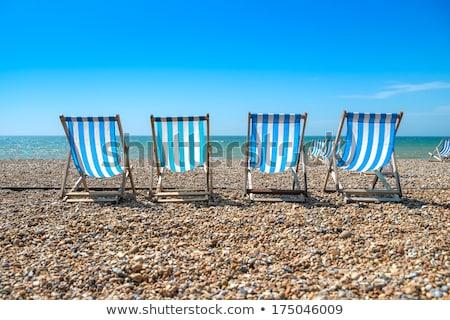 4 deck chairs on brighton beach stock photo © lucielang