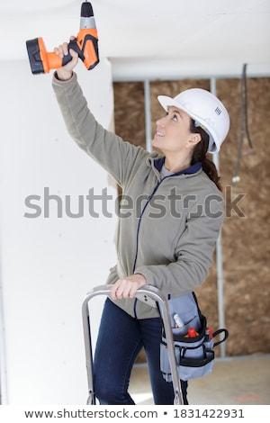 Woman with puncher on ladder Stock photo © Aikon