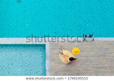 woman sitting on edge of swimming in pool stock photo © monkey_business