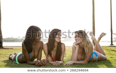 three women lying on their belly on the grass in a park backlit stock photo © brazilphoto