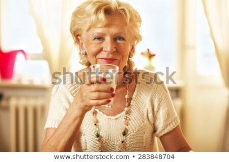 SMiling woman holding glass with yogurt Stock photo © deandrobot
