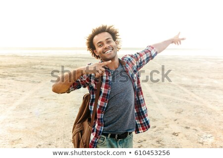 cheerful young african man pointing away with both hands stock photo © deandrobot