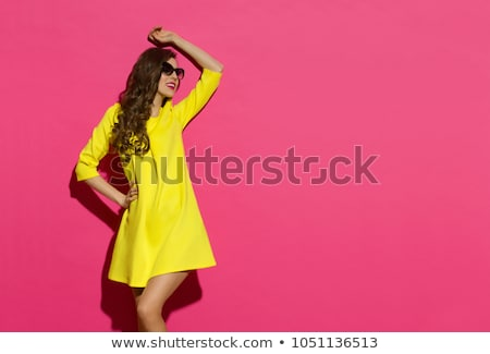 Woman in yellow dress standing and looking away stock photo © deandrobot