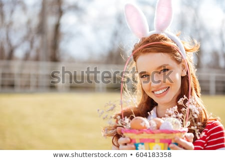 red head girl wearing easter bunny ears outdoors stock photo © deandrobot