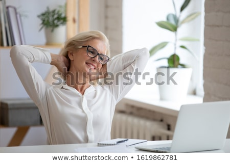 happy smiling blond woman sitting behind laptop and daydreaming stock photo © lordalea
