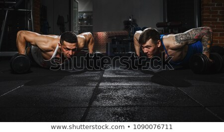 young concentrated fitness man doing workout with heavy barbell stock photo © deandrobot