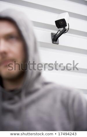 Megfigyelés kamera fiatalember kapucnis pulóver épület Stock fotó © monkey_business