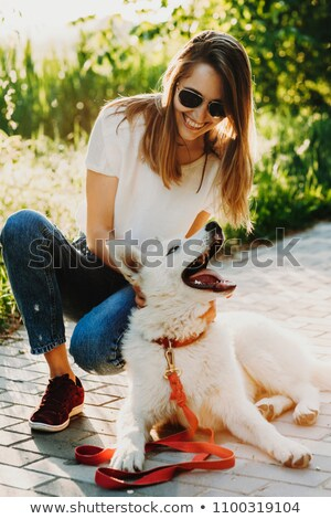 Cute girl laughing while playing with her dog Stock photo © ozgur