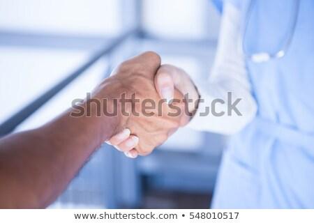 Médecins serrer la main couloir hôpital femme Photo stock © wavebreak_media