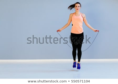 Smiling young woman with skipping rope Stock photo © deandrobot