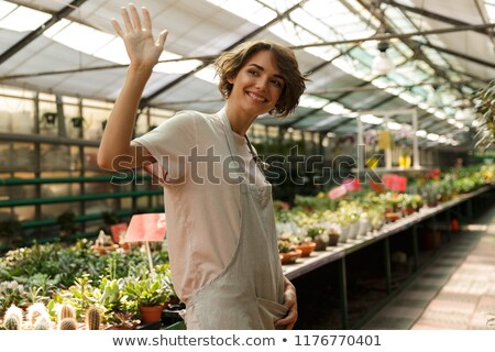 emotional cute woman gardener standing over flowers plants in greenhouse stock photo © deandrobot