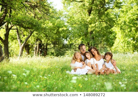 family sitting on a meadow in summer or spring stock photo © kzenon