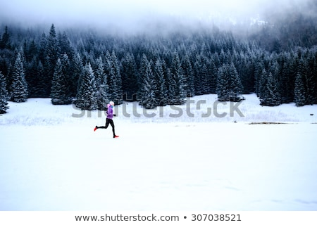 girl trail running on snow in winter mountains stock photo © blasbike