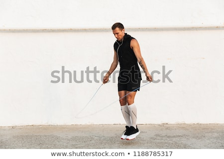 Sportsman outdoors at the beach make sport exercises with equipment. Stock photo © deandrobot