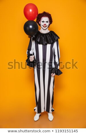 Cheerful man clown holding air balloons isolated Stock photo © deandrobot