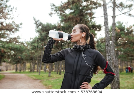 woman in headphones drinking water in park stock photo © dolgachov
