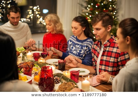 friends having home christmas dinner and praying Stock photo © dolgachov