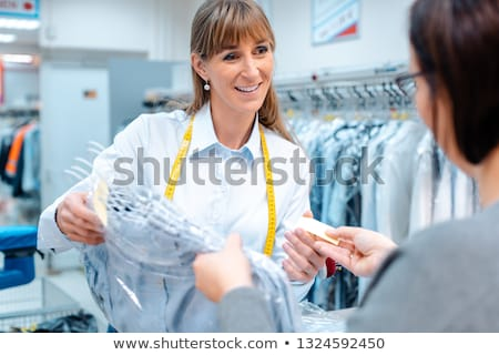 Customer in dry-cleaner shop getting back her clothes Stock photo © Kzenon