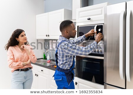Young Technician Adjusting Temperature Of Oven Stock photo © AndreyPopov