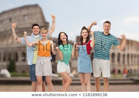 friends making fist pump gesture over coliseum Stock photo © dolgachov