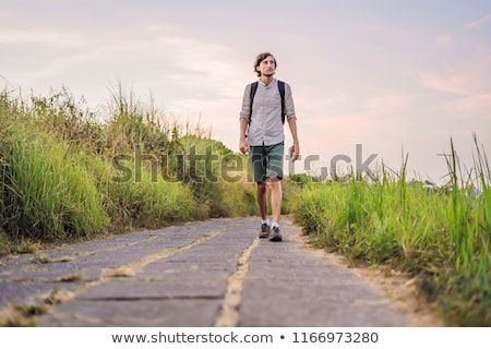 Man Traveler Campuhan Ridge Walk or Artists Walk sacred trail, Bali island, Indonesia On the Sunset. Stock photo © galitskaya