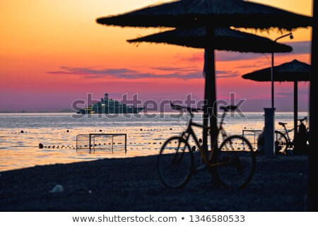 beach and parasols on colorful sunset with large yacht view stock photo © xbrchx