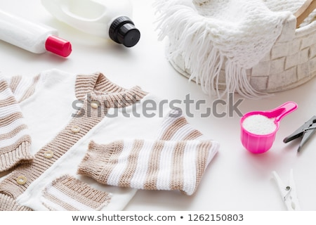 Warm knitted clothes and liquid laundry detergent Stock photo © Anneleven