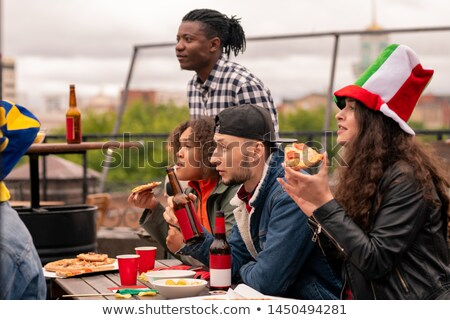 Young multicultural football fans in casualwear having pizza and beer Stock photo © pressmaster