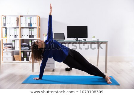 Businesswoman Doing Exercise On Exercise Mat Stock photo © AndreyPopov