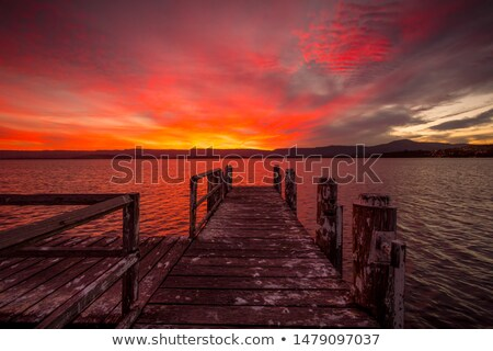 Burning red sunset  on the lake with timber jetty Stock photo © lovleah