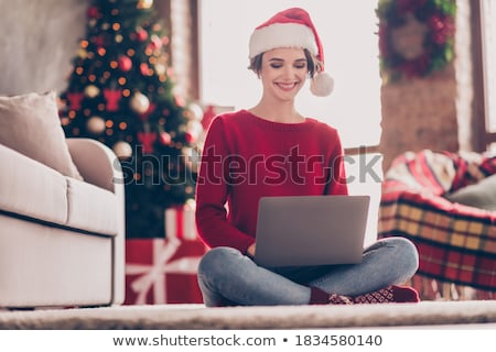 Beautiful young woman in red wearing santa hat. Stock photo © Nobilior