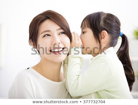 Heureux mère chuchotement secret fille maison Photo stock © dolgachov