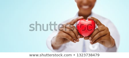 african american doctor hand holding red heart stock photo © dolgachov