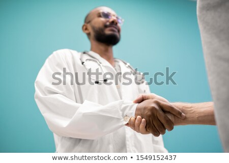 Handshake of young successful clinician in whitecoat and his recovered patient Stock photo © pressmaster