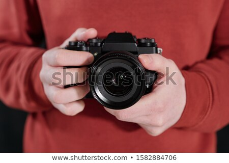 Hands of young male photographer in maroon sweatshirt holding new photocamera Stock photo © pressmaster
