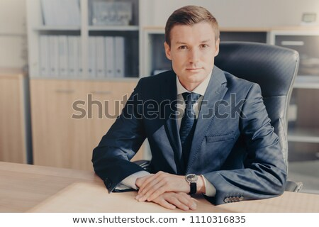 Professional male banker sits in cabinet, wears formal clothes, has confident expression while gives Stock photo © vkstudio