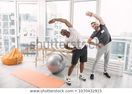 Therapist Assisting Male Patient While Doing Exercise Stock photo © AndreyPopov