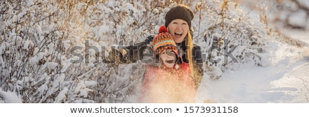 winter Mother and son throwing snowball at camera smiling happy having fun outdoors on snowing winte Stock photo © galitskaya
