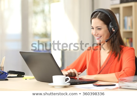 A beautiful young telephonist speaking on a headset  Stock photo © dacasdo