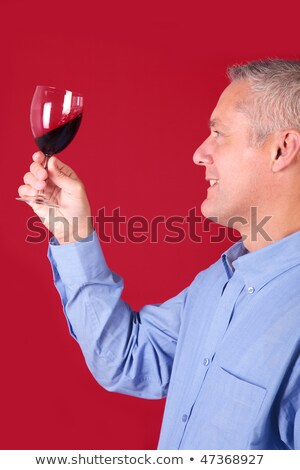 Man checking a glass of red wine for clarity Stock photo © RTimages