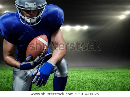Man kneeling on rugby pitch with hand on ball Stock photo © photography33