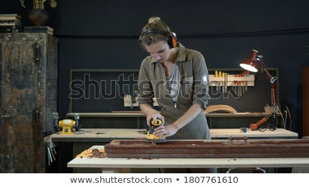 Female carpenter wearing protective muffs Stock photo © photography33