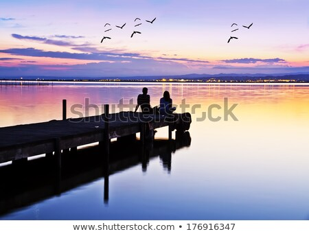 couple watching sunset at a pier stock photo © olandsfokus