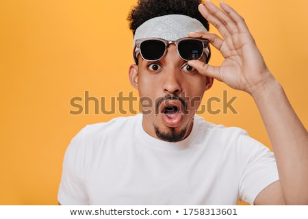 Surprised young fashion man taking off his sunglasses Stock photo © feedough