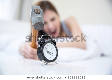 woman not wanting to get up taking a hammer to her alarm clock stock photo © deandrobot