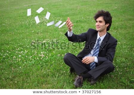 Businessman sitting  on the meadow and throwing paper cards Stock photo © Paha_L