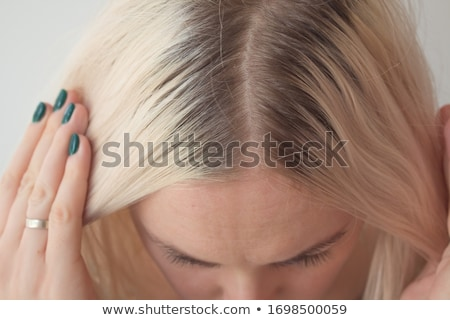 Female client with dark hair and hairdresser making hairdo Stock photo © deandrobot