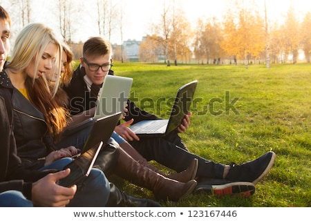 pretty young blond girl with laptop in the park stock photo © lithian